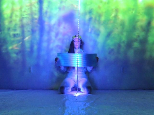 Louise Michel, agenouillée devant un mur illuminé de couleurs vives, fait face à la caméra et tient un objet rectangulaire brillant des deux mains à hauteur de la poitrine. Une guirlande lumineuse est suspendue devant elle. L'image est principalement bleue, verte et violette.